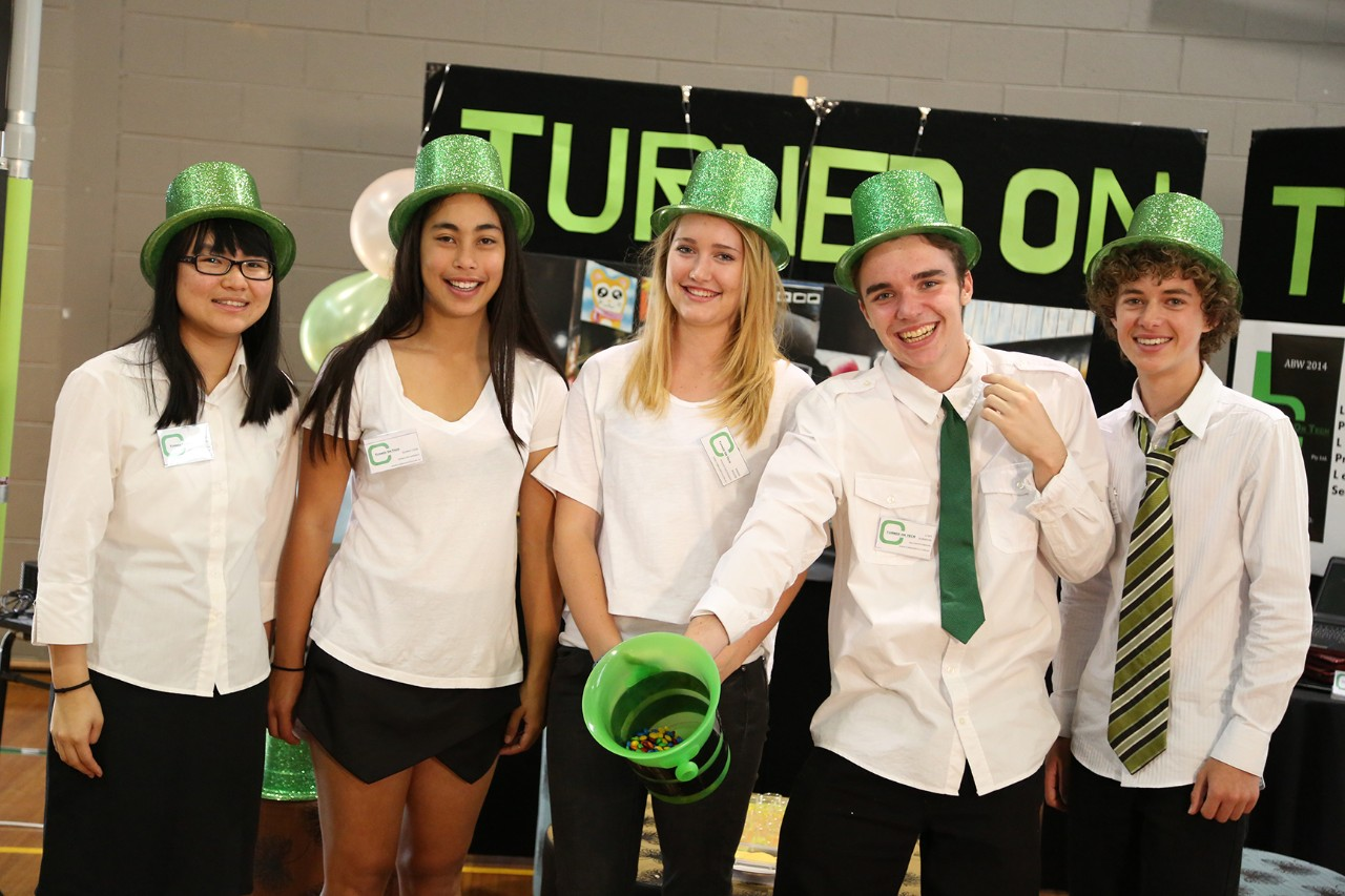 Students dressed in white shirts, sparkly green hats and green ties.